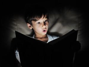 kid reading book light in darkness